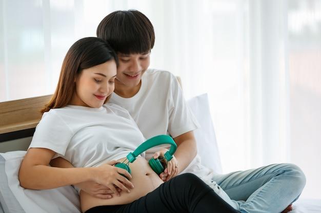 젊은 남자와 임산부는 아무렇지도 않게 미소 짓고 침대에 앉아 드레스를 입고 있습니다. 남편과 아내는 여성의 뱃속에 녹색 헤드폰을 착용했습니다. 편안하고 좋은 느낌의 개념입니다.