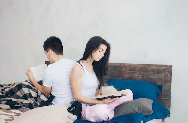 젊은 남자와 여자가 침대에 앉아 책을 읽고있다