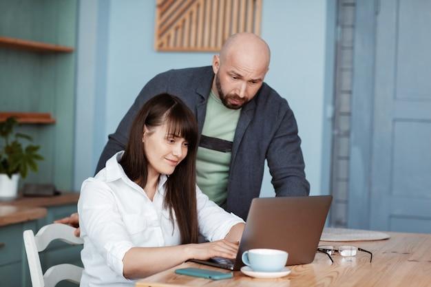 젊은 남자와 여자는 노트북을 사용하여 집에서 일