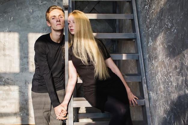 Молодой человек и молодая блондинка с длинными волосами. проблемы и трудности в отношениях. сложная ситуация в жизни. концептуальная фотография. актерская игра. жесткие тени показать чувства. скрыть чувства.