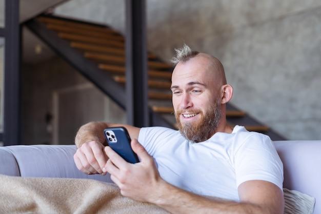 自宅のソファに座っている若い男性が、心地よい暖かい毛布を持って外れ、携帯電話を持ってニュースを読む