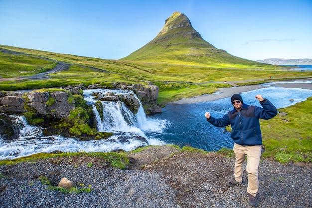 여름 아침 폭포에서 kirkjufellsfoss의 젊은 남자. 아이슬란드