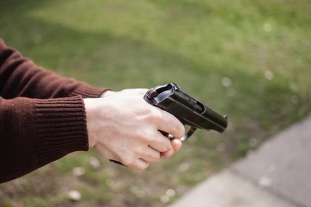 Молодой человек стреляет из ружья в зеленую траву. огнестрельное оружие