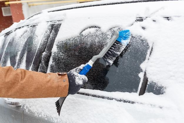 若い男が車から雪をきれいにします。冬のカーケア
