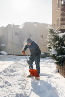 晴れて凍るような日に、若い男が家の前の雪を晴らします。雪から通りを掃除する。