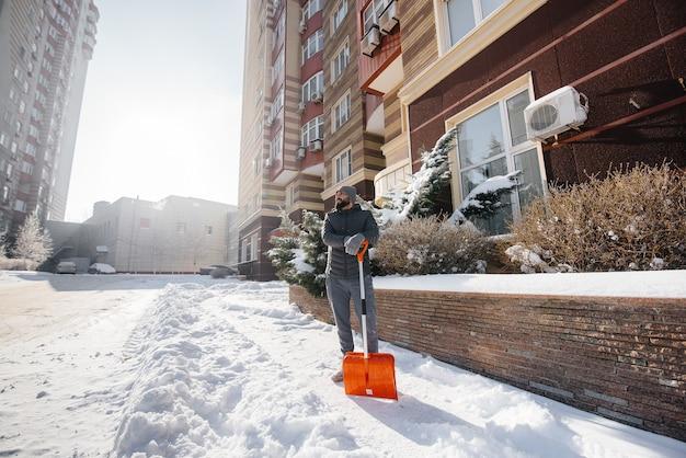 晴れて凍るような日に、若い男が家の前の雪を晴らします。