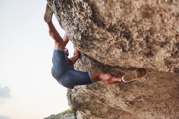 若い男の登山家が岩を登ります。