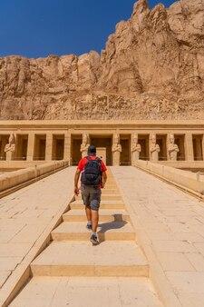 ルクソールにあるハトシェプスト女王の葬祭殿への階段を登る若い男。エジプト