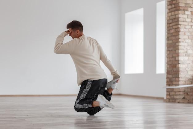 Молодой человек танцует брейк-данс, стоя на ноге и держась за голову в современной студии, у стены из белых стен.