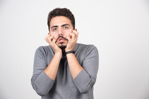 白い壁の上で変な顔をしている若い男。