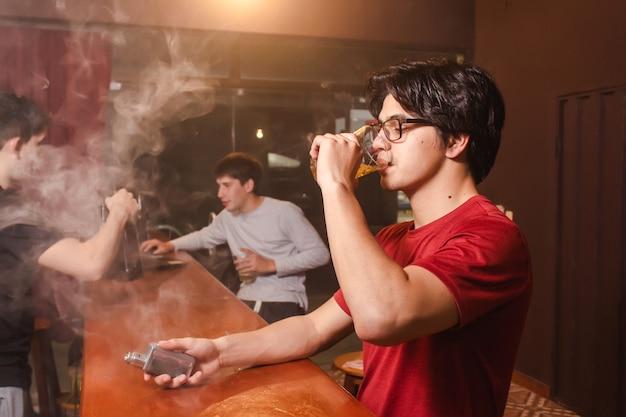 ビールを飲み、バーで友達とたばこを吸う若い男。