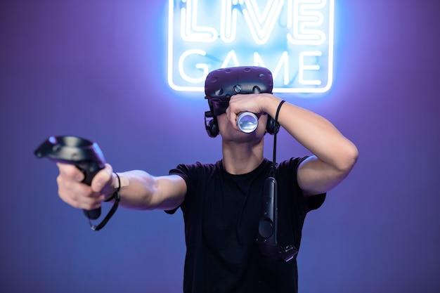 Молодой человек во время игры пьет энергию.