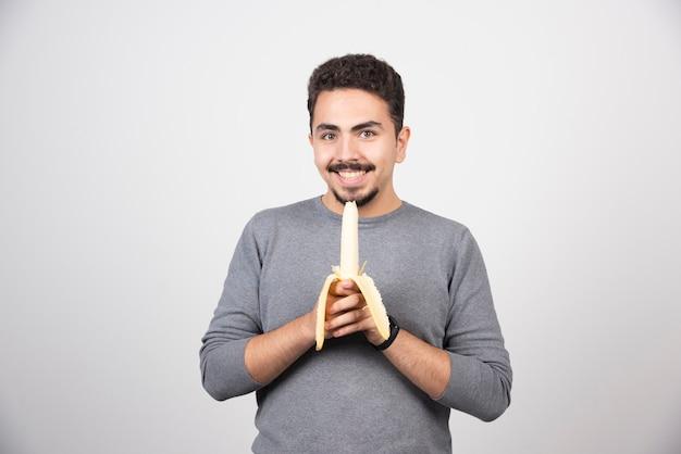 흰 벽 위에 바나나를 먹는 젊은 남자.