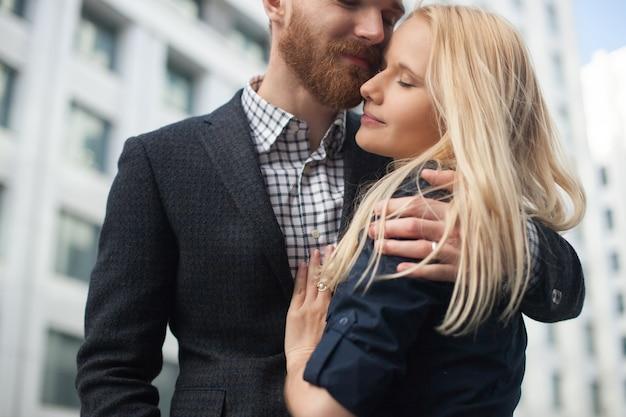 Молодой человек обнимает девушку в городе
