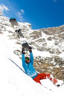Молодой человек в лыжной одежде с лыжными очками, катается на лыжах в горах рядом с красивым пейзажем
