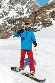 Молодой человек, одетый в лыжную одежду с лыжными очками, катается на лыжах в горах