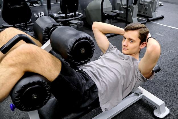 若い男がジムのシミュレーターで運動します。筋力を鍛えます。健康的なライフスタイルの概念。