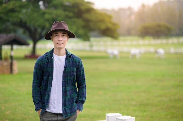 Фермер молодой человек работает на красивый пейзаж поля страны на рассвете