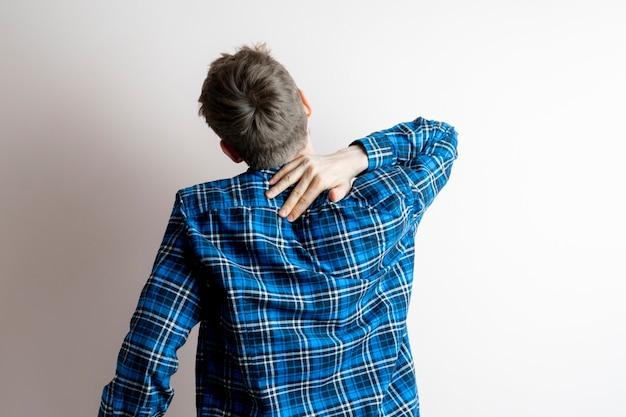 孤立したひどい痛みの腰痛の概念を感じている若い男