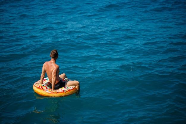 若い男が青い水で海の膨脹可能なエアリングサークルに浮かんでいます。幸せな晴れた日のお祝いの休日。休暇の概念、上面図。