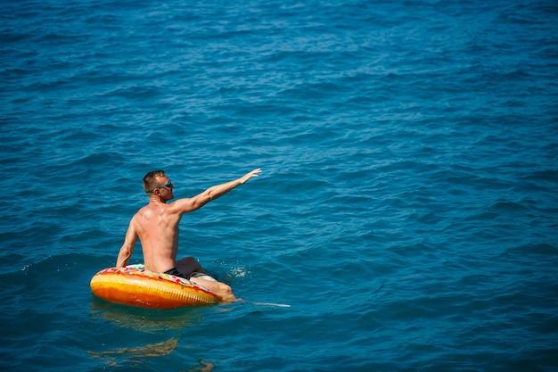 Молодой человек плывет по надувному кругу воздушного кольца в море с голубой водой. праздничный праздник в счастливый солнечный день. концепция отпуска, вид сверху.