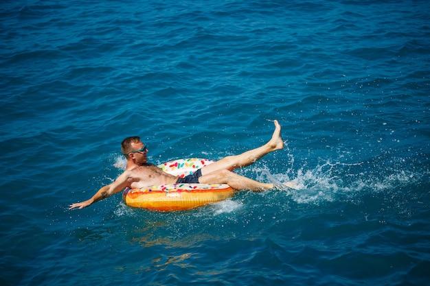 한 젊은이가 푸른 물이 있는 바다에서 팽창식 에어 링 원 위에 떠 있습니다. 행복한 화창한 날에 축제 휴가입니다.