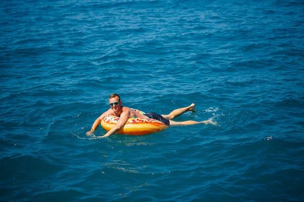 若い男が青い水で海の膨脹可能なエアリングサークルに浮かんでいます。幸せな晴れた日のお祝いの休日。
