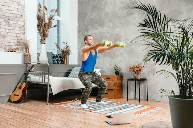若い男が自宅でスポーツに出かけ、ラップトップからオンラインでトレーニングする