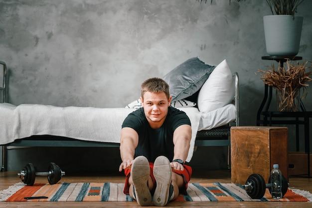 若い男が自宅でスポーツに出かける、電話からのオンライントレーニング