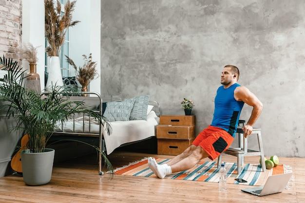 젊은 남자가 집에서 스포츠, 온라인 운동에 들어갑니다.