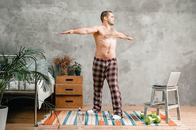 若い男が自宅でスポーツ、オンライントレーニングに参加します