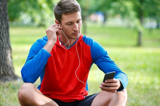 Молодой человек отдыхает после тренировки на открытом воздухе