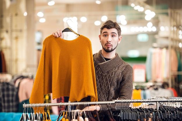 그의 여자 친구가 옷가게에서 올바른 스웨터를 찾도록 도와주는 청년