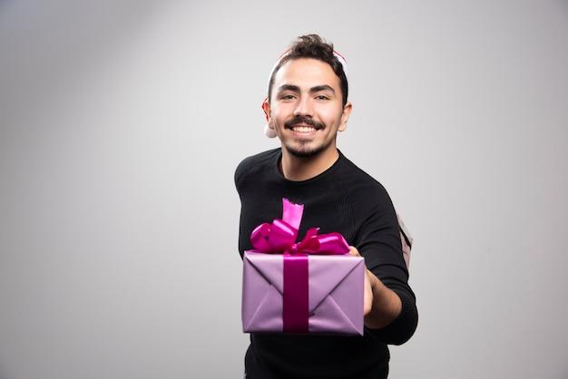 회색 벽 위에 선물 상자를 들고 젊은 남자.
