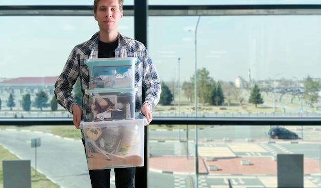 中に物が保管されているプラスチックの箱の容器を持っている若い男