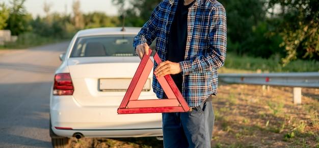 빨간색 삼각형을 들고 도로에 두는 젊은 남자, 교통 사고의 신호