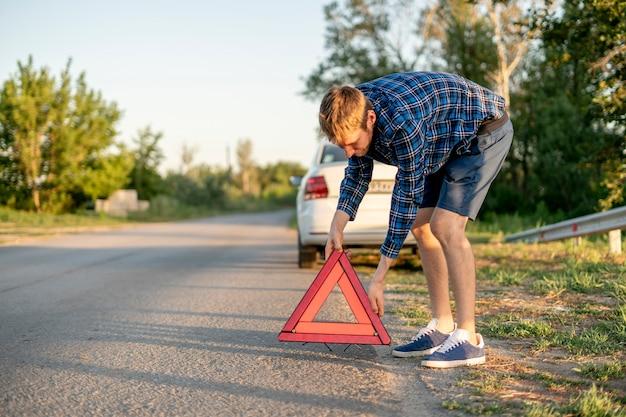 Молодой человек держит красный треугольник и ставит его на дорогу, знак автокатастрофы