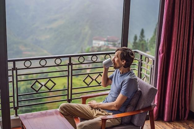 Молодой человек держит чашку кофе, сидя на стуле на балконе, глядя на горы и зелень