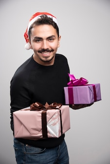 Молодой человек держит подарочные коробки над серой стеной.