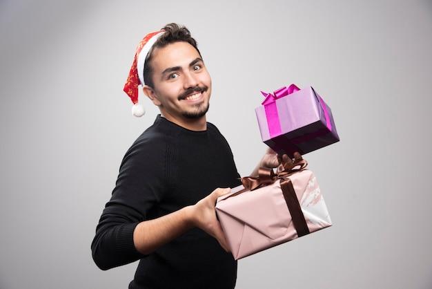회색 벽에 선물 상자를 들고 젊은 남자.