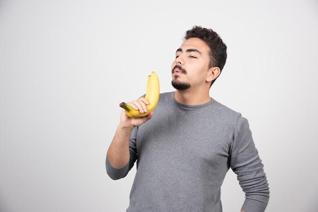 두 개의 신선한 바나나를 들고 젊은 남자.