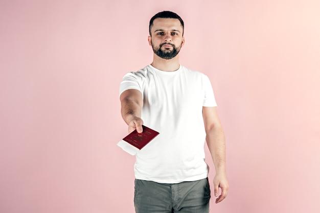 若い男が手にパスポートを持っています。旅行、移住、休暇。