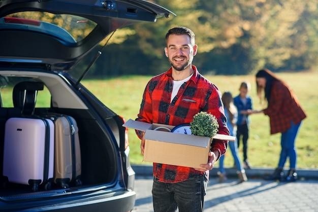Молодой человек держит картонную коробку, разгружая багаж из семейного автомобиля после переезда в новый дом.