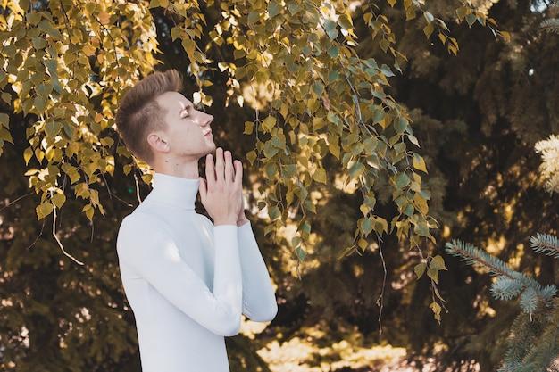 Молодой человек держит руки перед собой на осеннем фоне.