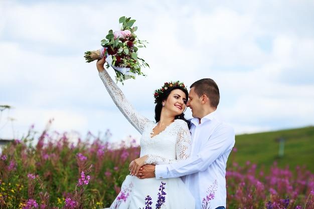 Молодой человек держит невесту в горах.