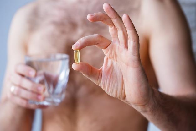 若い男は彼の手にビタミンとコップ一杯の水を持っています。免疫ピル