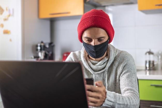 검은 얼굴 마스크에 젊은 남자가 집에서 일하는 동안 노트북과 휴대 전화를 사용하고 있습니다