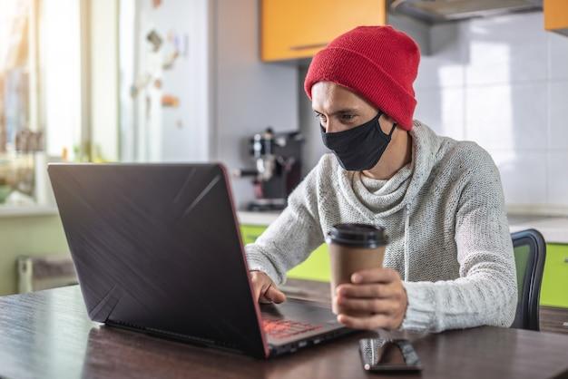 검은 보호 얼굴 마스크에 젊은 남자가 집에서 작업하는 동안 노트북을 사용하고 있습니다