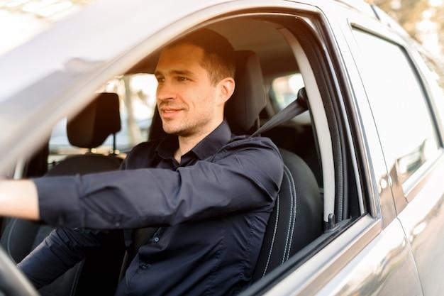자신의 차를 운전하는 어두운 셔츠에 젊은 남자. 긍정적이고 자신감있는 택시 기사