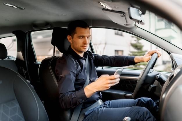 Молодой человек в темной рубашке за рулем своего автомобиля использует смартфон или телефон. концепция многозадачности